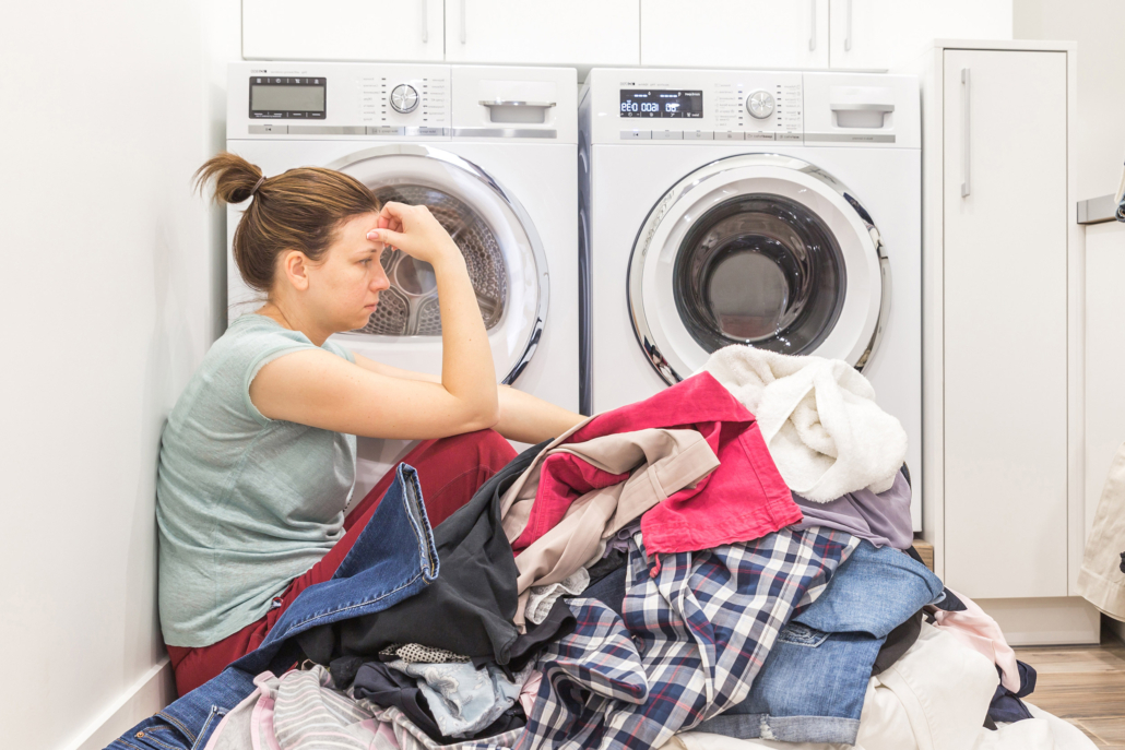Upset woman in laudry room sitting ona floor with dirty clothes